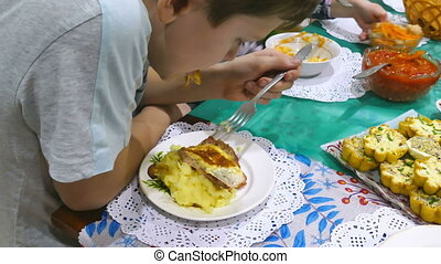 kids eat - boy at the table eating meat chop with potatoes...
