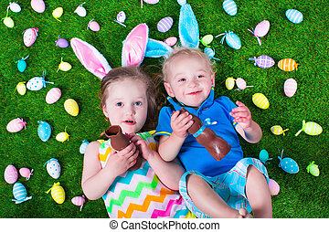 Kids eating chocolate rabbit on Easter egg hunt - Children...