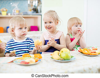 kids eating fruits in kindergarten dinning room