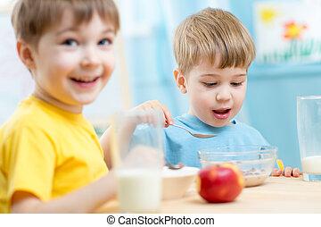 kids eating healthy food in kindergarten or nursery