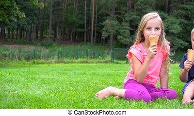 kids eating icecream outdoors - two kids eating icecream...