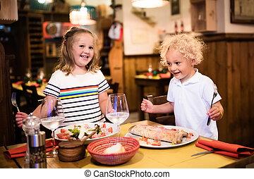 Kids eating pizza in Italian restaurant