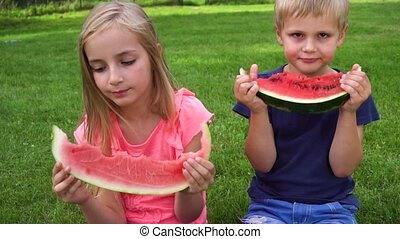kids eating watermelon outdoors