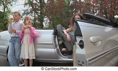 kids eats bread and drink water, parents sit in cabriolet
