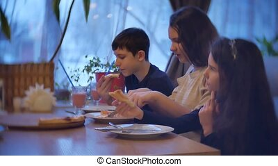 kids family group of people eat pizza at a cafe. close-up children teens eating fast food in indoors cafe slow motion video