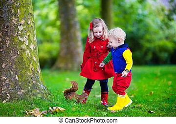 Kids feeding squirrel in autumn park. Little boy and girl in...