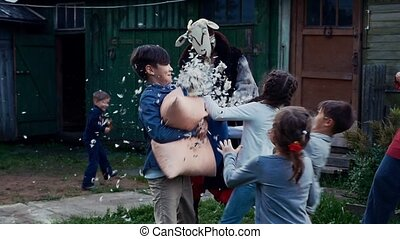 Kids fight pillow in country house yard. Man dance in cow costume. Feathers.