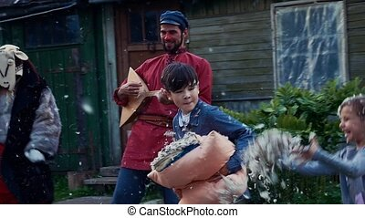 Kids fight pillows in yard of country house. Entertainment....