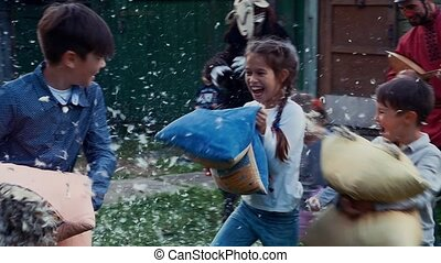 Kids fight pillows in yard of country house. Feathers....