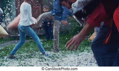 Kids fight pillows in yard of country house. Many feathers...