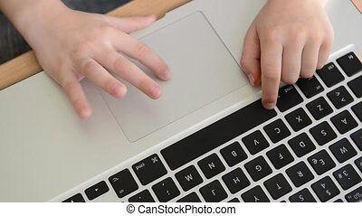 Kids finger using a laptop touch pad. child playing...