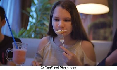 kids girl group family of people eat pizza at a cafe. close-up children teens eating fast food in indoors cafe slow motion video