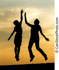 Kids giving a high five at sunset.