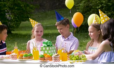kids giving presents to birthday child at party - holidays,...
