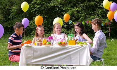 kids giving presents to birthday child at party