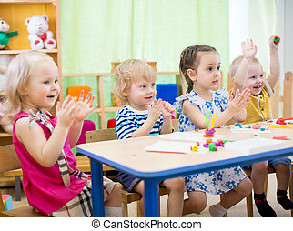 kids group learning arts and crafts in day care centre or...