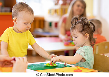 Kids group making arts and crafts in kindergarten. Children on lesson in daycare centre