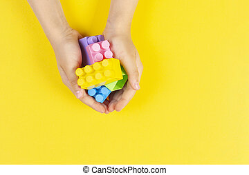 Kids hands hold colorful plastic construction blocks on yellow background