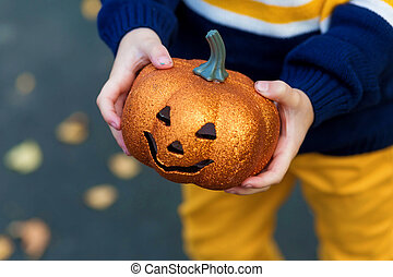 Kid's hands holding a toy pumpkin lantern for the holiday halloween