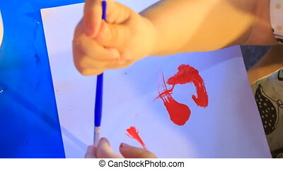 Kid's Hands Paint Red Lines with Br