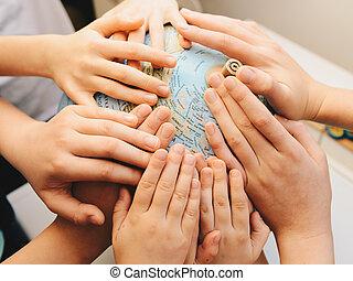 Kids hands together on globe - diversity concept