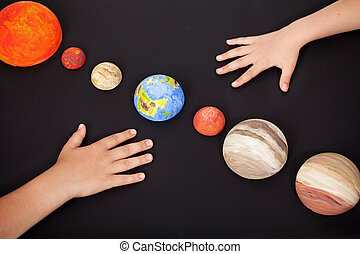 Kids hands with the planets of the solar system - science...