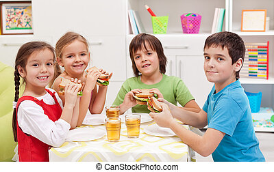 Kids having a snack in their room - Happy kids having a...