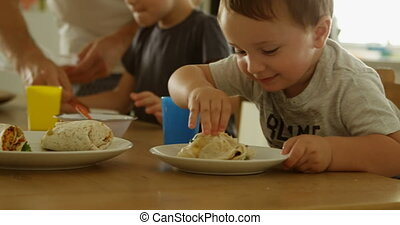 Kids having food with father on dining table 4k