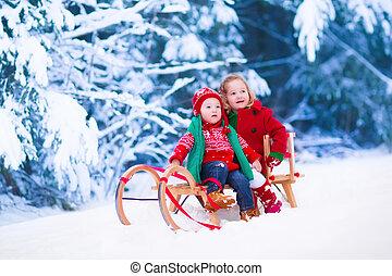 Kids having fun on a sleigh ride in winter