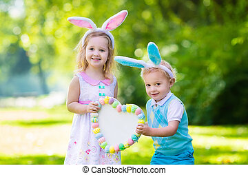 Kids having fun on Easter egg hunt - Little boy and girl ...