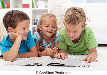 Kids having fun reading - Three kids having fun reading a...