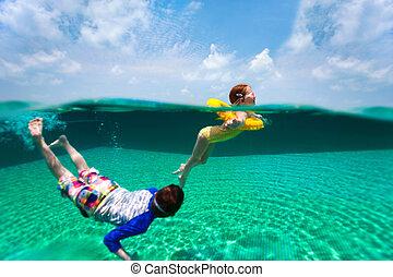 Kids having fun swimming on summer vacation - Split above...