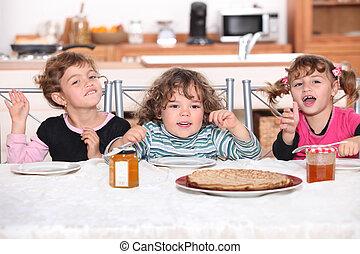 Kids having pancakes for breakfast