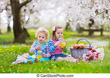 Kids having picnic in blooming garden - Little children...