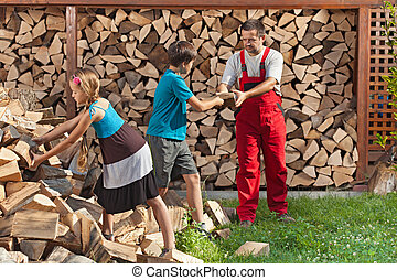 Kids helping their father to stack the firewood