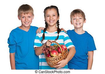 Kids hold a basket with vegetables