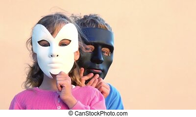 kids hold masks near faces and boy hides behind girl - Two...