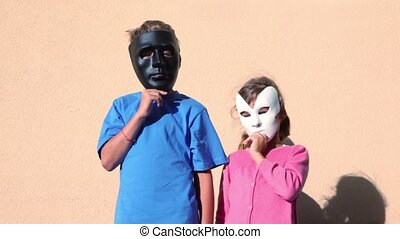 kids hold masks near faces, then turn and watch to each...