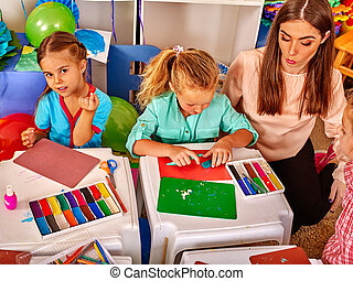Kids holding colored paper on table in kindergarten . -...