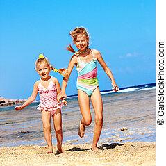 Kids holding hands running on beach.