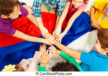 Kids holding their hands together above the flag