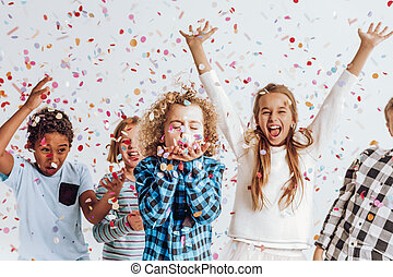 Kids in a room full of confetti