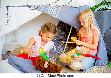 Kids in a wigwam - Two girls playing together in a wigwam in...