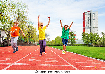 Kids in colorful uniforms with arms up running the marathon on the finish line on the stadium