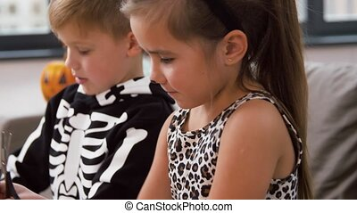 kids in halloween costumes doing crafts at home - halloween...