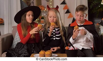 kids in halloween costumes eating cupcakes at home - ...