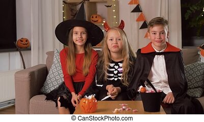 kids in halloween costumes having fun at home