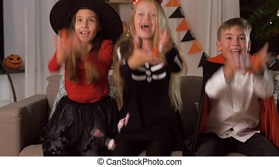 kids in halloween costumes throw candies at home - halloween...