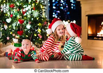 Kids in pajamas under Christmas tree