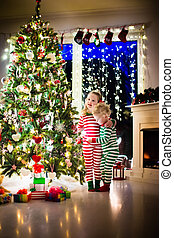 Kids in pajamas under Christmas tree - Happy little kids in...